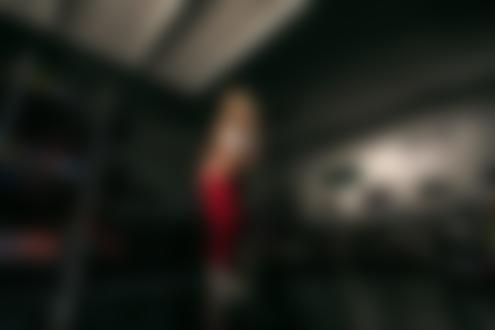 Обои Блондинка в белом лифчике и в приспущенном красном комбинезоне стоит в гаражном помещении