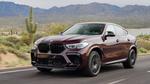 Обои Мужчина едет за рулем бордового BMW X6 2019 по трассе на фоне гор