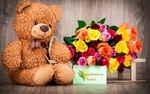 Обои Плюшевый мишка сидит рядом с букетом роз и открыткой с надписью с праздником весны