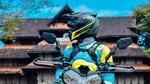 Обои Мотоциклист в шлеме на фоне дома