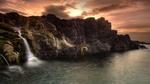 Обои Скала с водопадом у моря на фоне заходящего солнца