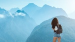 Обои Девушка в шортиках и рюкзаком стоит на фоне покрытых дымкой гор