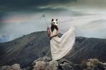 Обои Девушка в белом платье с маской на голове держит в руке сломанный зонт