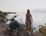 Обои Девушка стоит спиной к нам рядом с мотоциклом на фоне моря