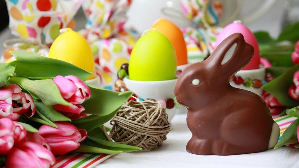 Обои для рабочего стола Обои шоколадный заець стоит на столе с тюльпанами яйцами и клубком ниток