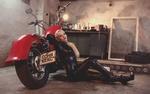 Обои Девушка - блондинка в латексе сидит у мотоцикла в гараже