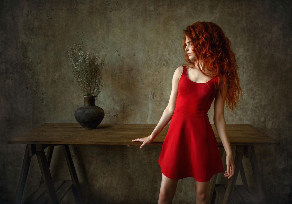 Обои для рабочего стола Рыжеволосая девушка в красном платье стоит у стола, фотограф Albert Lesnoy