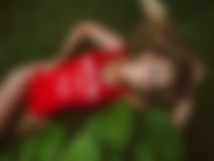 Обои Девушка - блондинка в красном боди лежит на траве