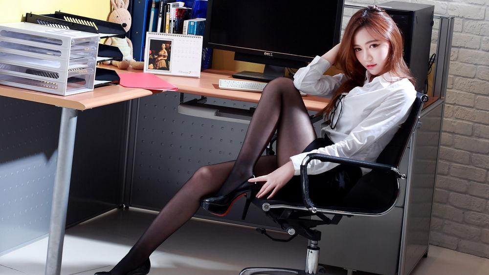 Обои для рабочего стола Девушка с азиатской внешностью сидит на офисном кресле подняв ногу