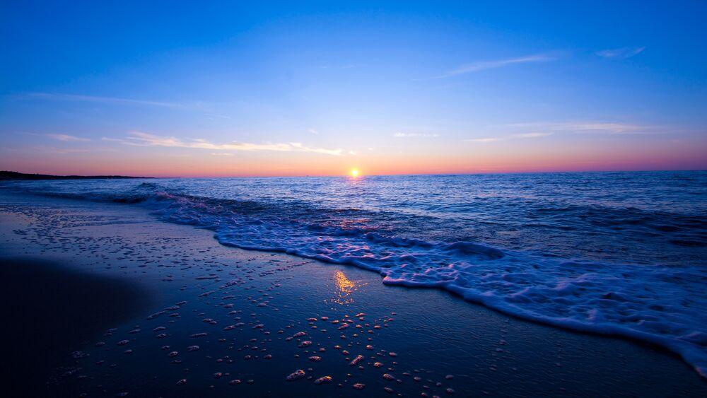Обои для рабочего стола Вечерний берег моря на фоне заката солнца