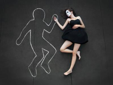 Фото девушка лежит на асфальте вместе с нарисованным человеком