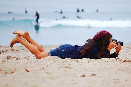 Фото Девушка с фотоаппаратом на пляже