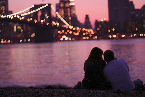 И девушка сидят на берегу реки и