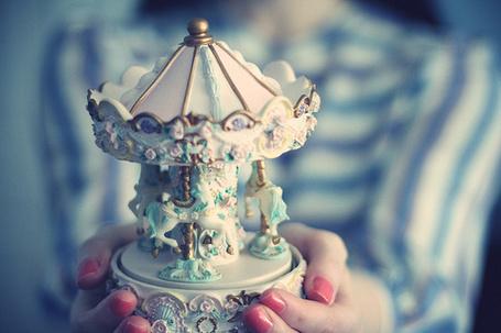 Фото Девушка держит в руках игрушечную карусель (© Electraa), добавлено: 19.02.2011 12:39