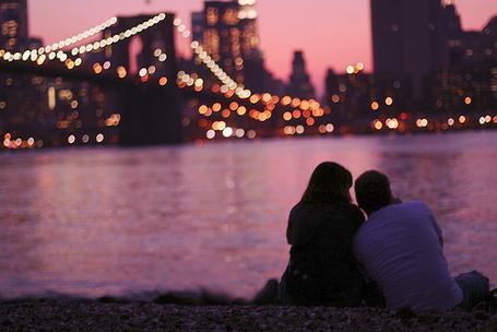 Фото Парень и девушка сидят на берегу реки и смотят на вечерний город