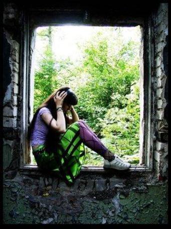 Фото Девушка в заброшенном доме сидит в проеме окна