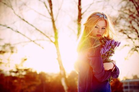 Фото Девушка в лучах солнца с букетом цветов в руках