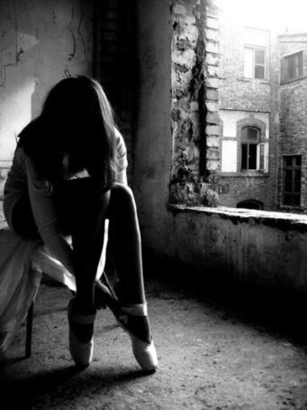 Фото Девушка завязывает пуанты в заброшенном доме