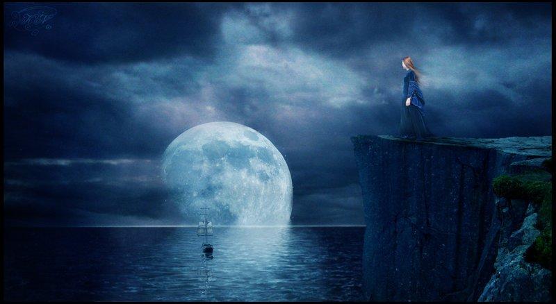 Фото Девушка стоя у обрыва смотрит на море
