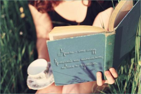Фото Девушка сидит в траве с чашкой на блюдце и книгой в руках (книга - это сосуд, который нас наполняет, но сам не пустеет)