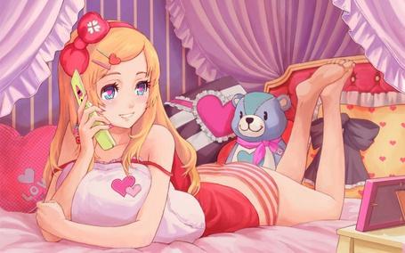 Фото Красивая девушка блондинка лежит на кровати и болтает по телефону