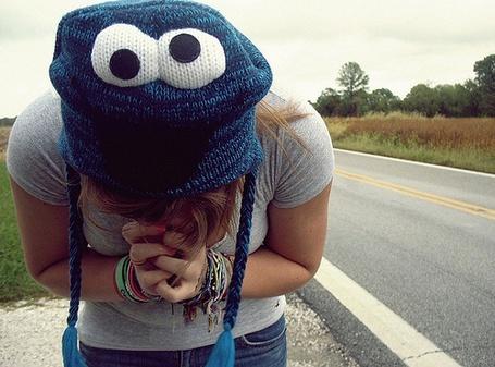 Фото Девушка возле дороги в смешной вязанной шапочке с глазками