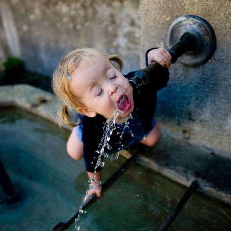 Фото Маленькая девочка пьёт воду на улице