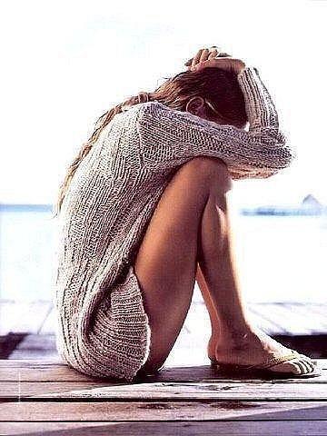 Фото Девушка сидит на мостике, закрыв голову руками