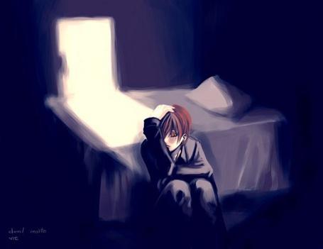 Фото Парень сидит в тёмной комнате около кровати