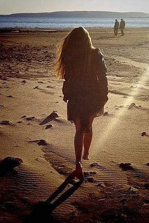 Фото Девушка гуляет по пляжу в лучах солнца
