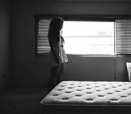 Фото Девушка стоит у окна в полупустой комнате