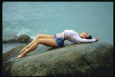 Фото Девушка лежит в экстровагантной позе на камнях у моря