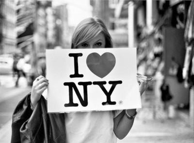 Фото Девушка держит табличку I♥NY(Я люблю Нью-Йорк)