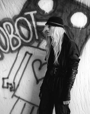 Фото Девушка в шляпе на фоне нарисованного на стене робота