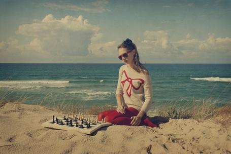 Фото Девушка играет в шахматы на пляже