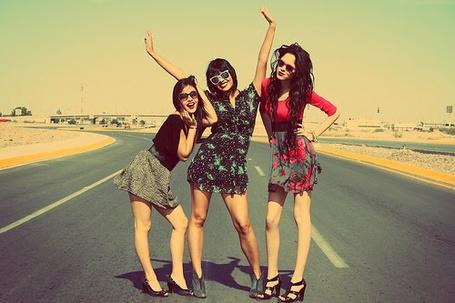 Фото Три веселых девушки в очках стоят на дороге
