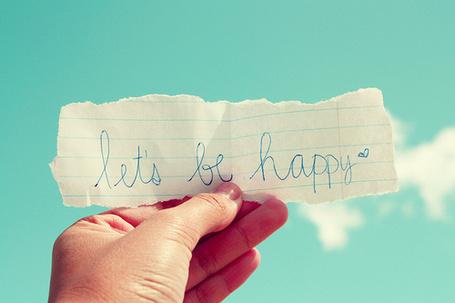 Фото Человеческая рука держит надпись 'Let's be happy' / 'Давайте будем счастливыми'