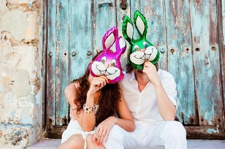 Фото Парень и девушка держат перед лицами гелевые шарики в форме зайцев