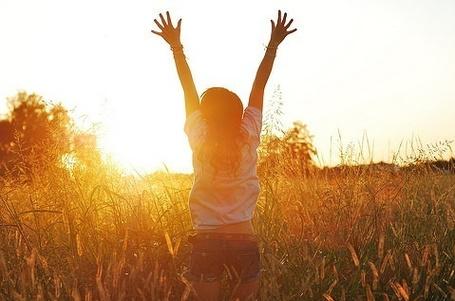 Фото Девушка бежит подняв руки в поле на встречу закату