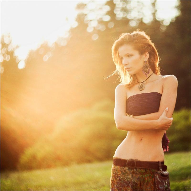 Фото Девушка на природе стоит в лучах солнца
