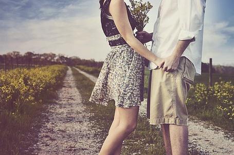 Фото Парень и девушка с букетом держатся за руки