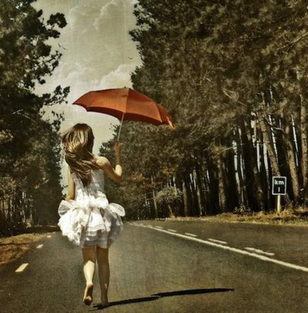 Фото Девушка в белом платье с зонтом в руках бежит по дороге