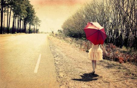 Фото Девушка с красным  зонтом гуляет по обочине дороги