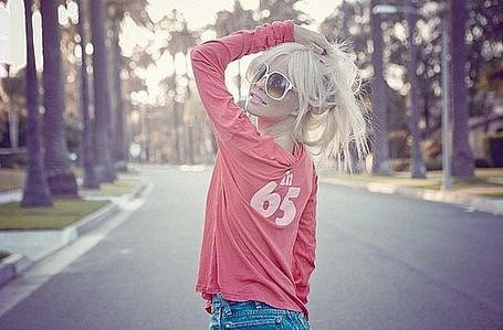 Фото Блондинка в розовой кофте и белых очках гуляет по дороге