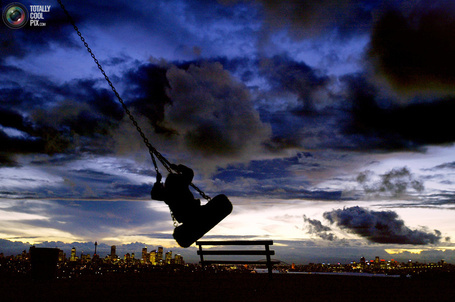 Фото Девушка катается на качелях вечером