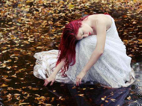 Фото Рыжая девушка с закрытыми глазами в белом платье сидит,трогая осенние листья в воде
