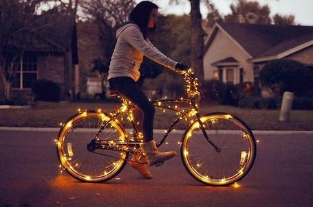 Фото Девушка едет на велосипеде со светящимися ободами