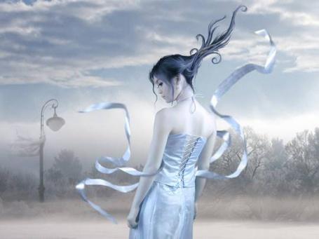 Фото Девушка в нежно голубом платье с равевающимися на ветру лентами