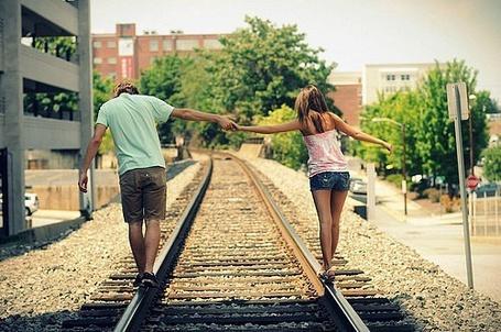 Фото Парень и девушка идут по железнодорожным путям, держась за руки
