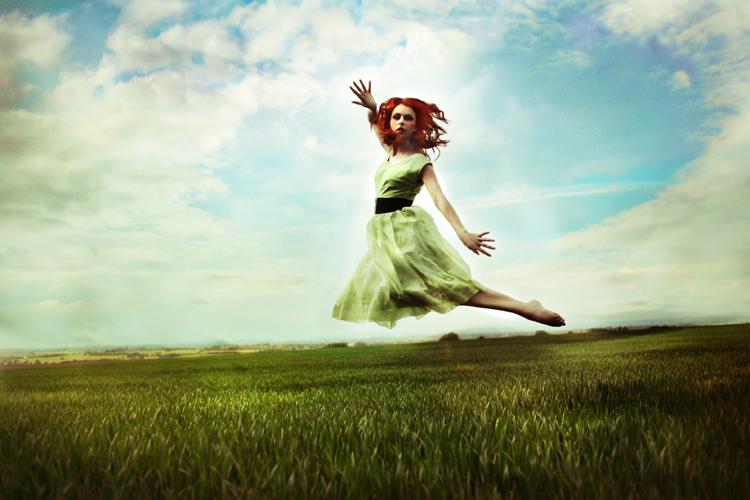 Фото Парящая в воздухе шатенка на фоне неба и зеленой травы
